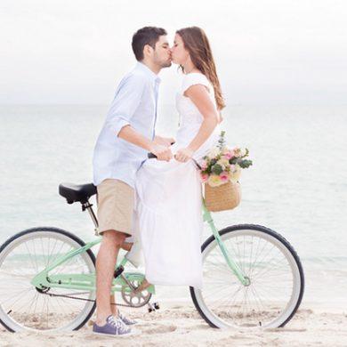 Couple kissing on a beach cruiser in South Beach.