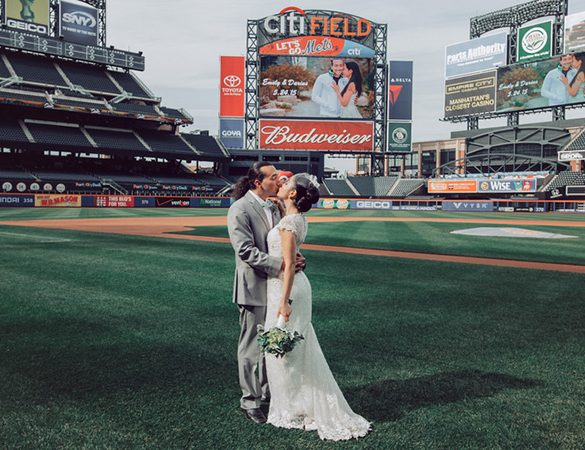 Bride and groom kissing on the Citi Field Ballpark green