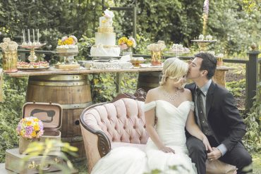 Couple lounging on vintage couch in front of a rustic dessert table.
