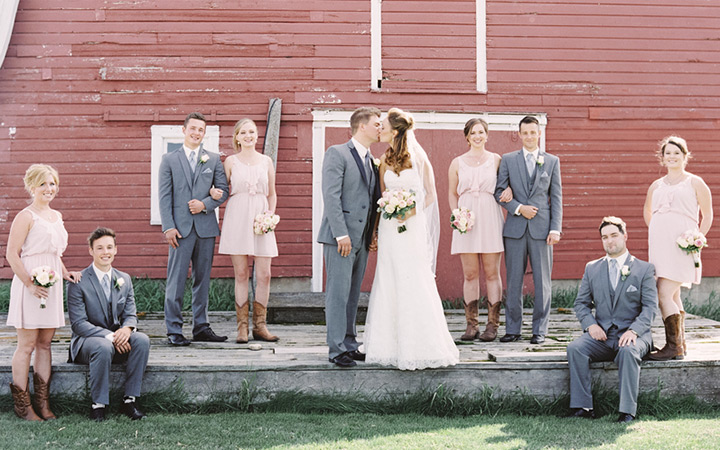 Wedding party posing in front of a red barn.