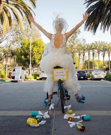 Bride and groom riding off on a motorcycle.
