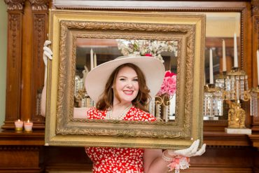 bride to be posing behind a picture frame