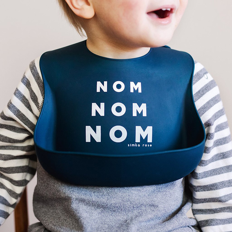 Child wearing Nom Nom Nom silicone bib