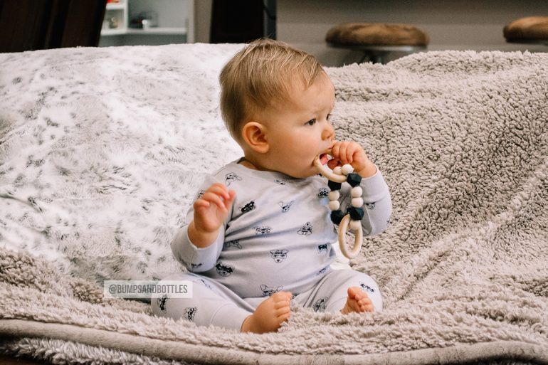 Baby boy playing with natural teether