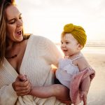 Mom holding baby wearing mustard top knot baby turban