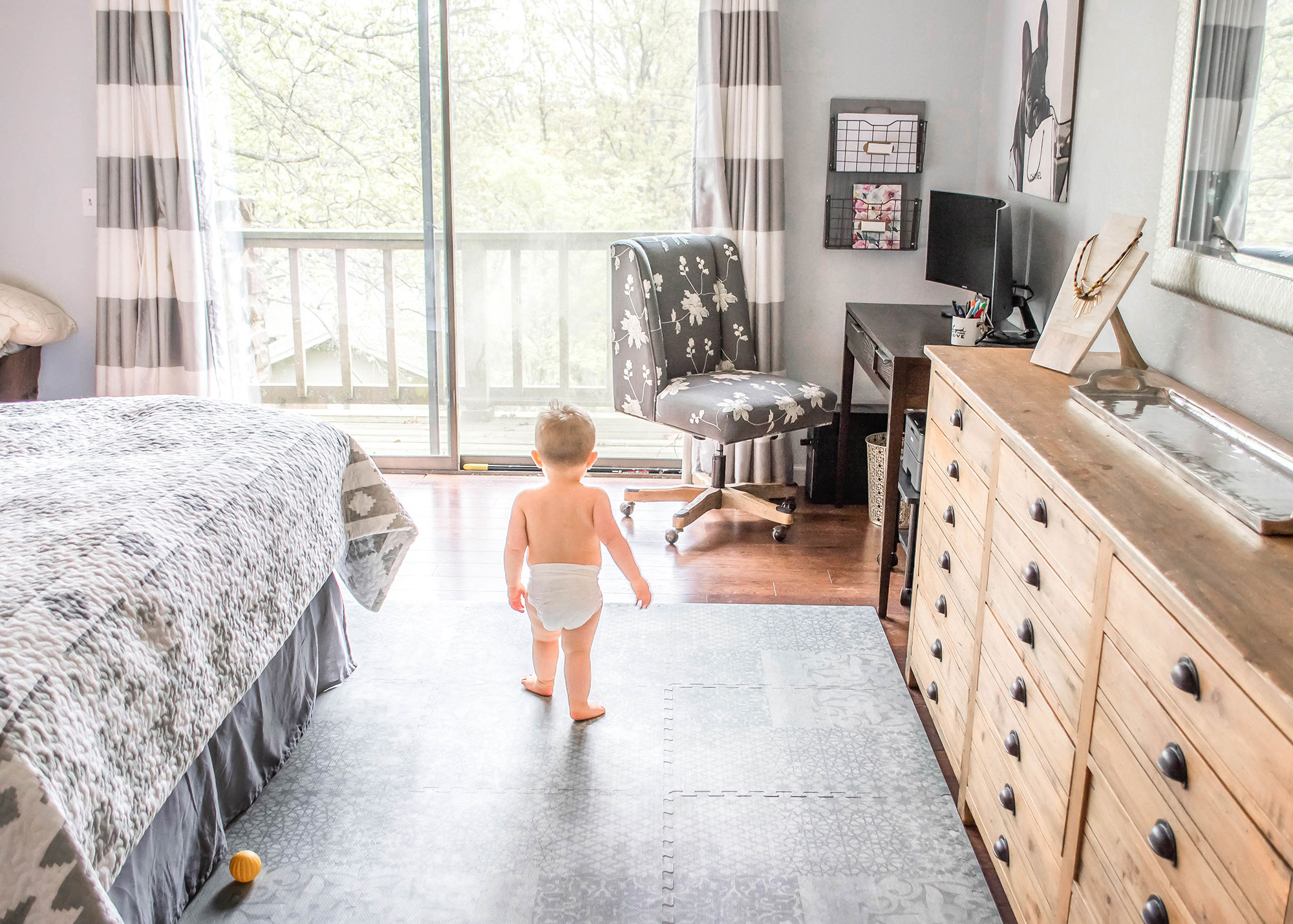 Little boy walking on a Little Nomad foam play mat in a home office